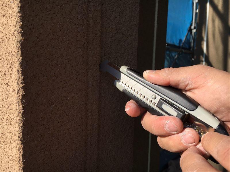 住宅外壁の旧シーリングを除去しようとカッターナイフを使用している